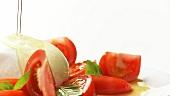 Tomaten, Mozzarella und Basilikum mit Olivenöl begiessen