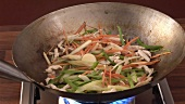 Tossing chicken and vegetables in a wok