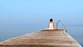 Junge Frau läuft auf einem Steg und setzt sich