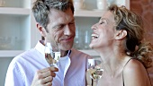 Man & woman clinking glasses of white wine, woman kissing man
