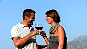 Man and woman clinking glasses of red wine out of doors