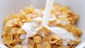Putting cornflakes into a bowl and pouring milk onto them