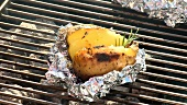Baked potato with rosemary on a barbecue