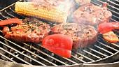 Schweinenackensteaks mit Maiskolben und Paprika auf dem Grill