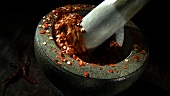 Crushing dried chillies in a mortar