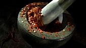 Getrocknete Chiliflocken in einem Mörser zerstossen
