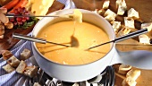 Dipping white bread into cheese fondue with fondue fork