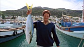 Fisherman holding freshly caught yellowtail