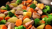Sautéing pork with broccoli, potatoes and carrots