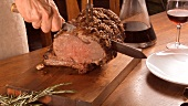 Roast prime rib steak being sliced and served with gravy