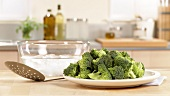 Broccoli florets, a slotted spoon and iced water (prepared for blanching)