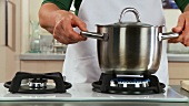 Blanching broccoli: placing a pot of water on a gas stove