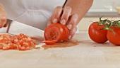 Tomate von der Rispe nehmen und in kleine Würfeln schneiden