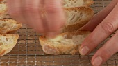 Garlic being rubbed onto slices of toasted bread