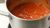 Simmering tomato sauce being stirred