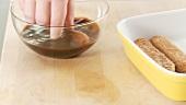 Preparing tiramisu: dunking sponge fingers in espresso