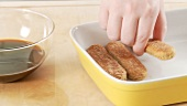 Preparing tiramisu: placing the sponge fingers in a dish