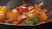 Peppers and onions being fried in a pan