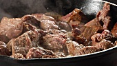 Beef being turned over in a pan
