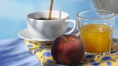 A breakfast tray at the pool: fruit juice, a peach and coffee being poured