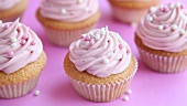 Cupcakes being decorated with pink cream and sugar pearls