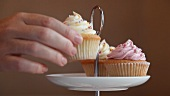 A hand placing a cupcake on a cake stand