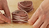 Beef fillet slices wrapped in bacon being secured with kitchen twine