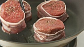 Barded beef fillet slices being placed in a pan