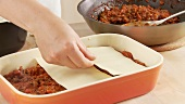 Minced meat sauce and lasagne sheets being layered in a baking dish