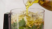 Olive oil being added to pesto ingredients in a mixer
