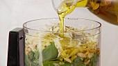 Olivenöl zu Pestozutaten in einen Mixer geben