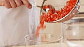 Diced tomatoes being tipped into a bowl