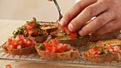 Baguettescheiben mit Tomaten-Basilikum-Mischung belegen