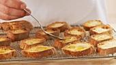 Baguettescheiben mit Olivenöl beträufeln