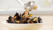Mussels in a white wine and tomato broth being served