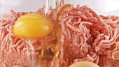 An egg and a bread being added to minced meat