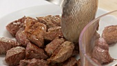 Fried pieces of meat being put on a plate