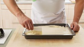 Sponge cake dough being spread in a baking tray