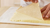Grease-proof paper being removed from sponge cake layers