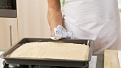 Sponge cake being removed from the oven and the edge being loosened