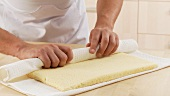 Sponge cake being rolled up with the aid of a cloth