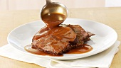 Beef pot roast being served with gravy