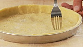 Shortcrust tart base being pierced with a fork