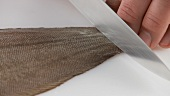 Seezunge vorbereiten: Die Haut am Schwanzende einschneiden