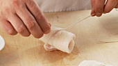 Plaice fillets being rolled up and tied with kitchen twine