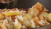 Bratkartoffeln mit Salz und Pfeffer würzen
