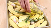 Prepared rosemary potatoes being drizzled with olive oil