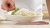 Risotto being sprinkled with parmesan and garnished with basil