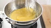 Egg cream being stirred over a bain marie