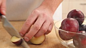 Plums being pitted and sliced